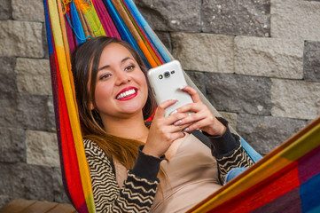 Close up of young beautiful woman in a hammock using her cellphone, in blurred background