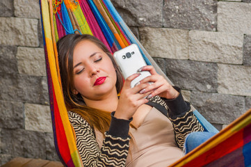 Close up of young beautiful woman sleeping in a hammock while she is with a cellphone in her hands, in blurred background