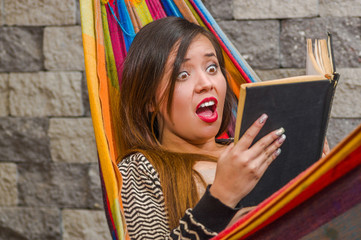 Close up of surprised young beautiful woman reading a book in a hammock, in blurred background