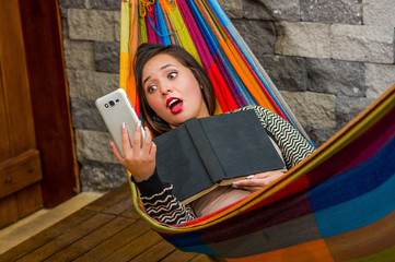 Close up of surprised young beautiful woman relaxing in a hammock and taking a selfie with her tablet while is holding a book with her other hand, blurred background