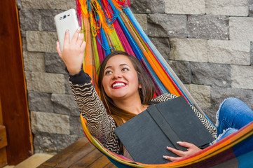 Close up of young beautiful woman relaxing in a hammock and taking a selfie with her tablet while is holding a book with her other hand, blurred background