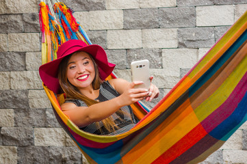 Close up of young beautiful woman wearing a red fashion hat and relaxing in a hammock and taking a selfie with her cellphone, in blurred background