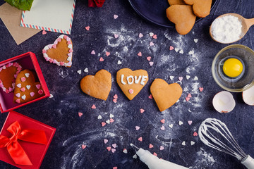 Homemade cookies in shape of heart with I Love you words as gift for lover on Valentine's day. Dark stone background with ingredients, flower and decor. Love gift concept. Selective focus. Copy space