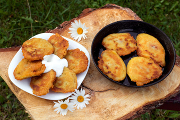Homemade potato pancakes with sour cream. Potato fritters on white plate on wooden brown background.