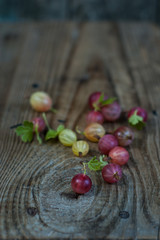 Many ripe berries of gooseberry on a wooden background.