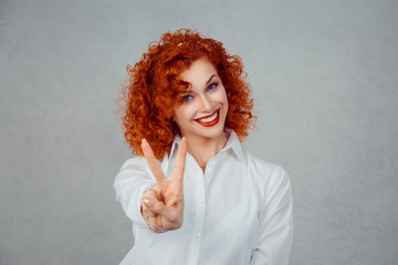 Peace, guys. Young redhead curly Girl With Victory Sign isolated on gray wall background.