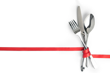 Fork, spoon and knife tied with a red ribbon isolated with copy space