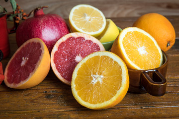 Tropical fruits with mix of lemons, oranges, grapefruit, pomegranate on a vintage wooden board