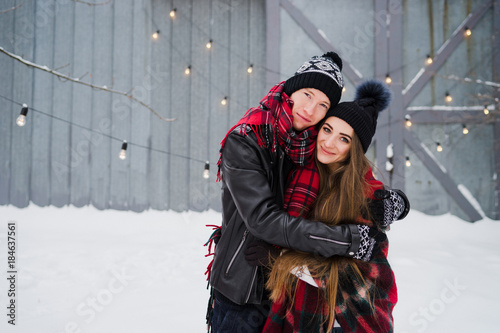 7d568120a0b Cheerful loving couple in warm cozy clothes hugging and warming up with  colorful blanket in the garden. Cold happy winter day. Holidays