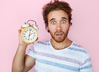 Shocked man posing with clock