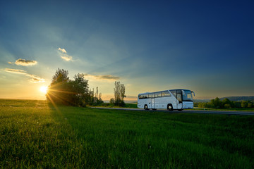 Fotobehang - White bus traveling on the road in a rural landscape at sunset