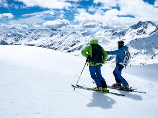 Winter extreme sport. A hiking trip on skis. Two skiers admire beautiful alpine landscapes. Italy resort Maso Corto.