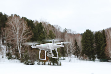 Quadrocopter, drone in flight against the background of a coniferous forest, in the mountains