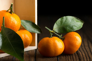 Fresh tangerines with leaves in wooden box on the table
