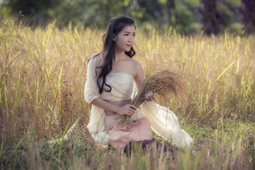 A good peasant woman dressed in a beautiful folk costume thinking in the wheat field, while harvesting in the background horizontally launched the picture.