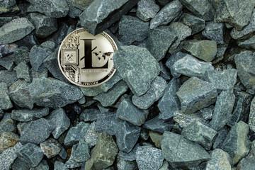 Silver coin litecoin in the grey gravel. Mining litecoin. Search litecoin.