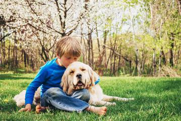Boys sitting in the garden kissing his golden retriever dog