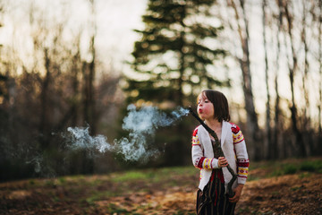 Girl holding a stick blowing out fire