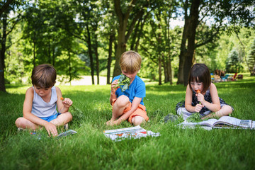 Three children sitting in a garden reading books and eating fresh vegetables