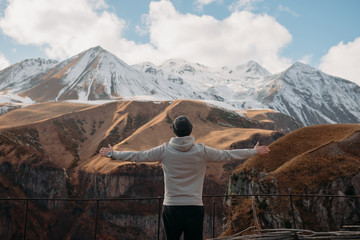 Man standing in mountains with his arms outstretched, Georgia