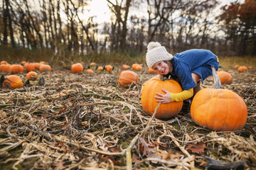 Girl trying to lift a pumpkin in a pumpkin patch