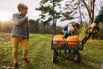 Father pulling three children in a wagon with pumpkins