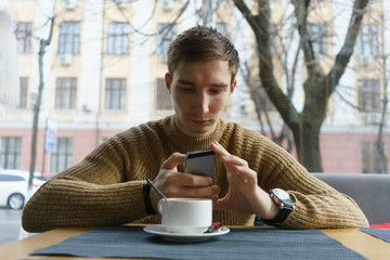 Man sitting in coffee shop reading text message on mobile phone