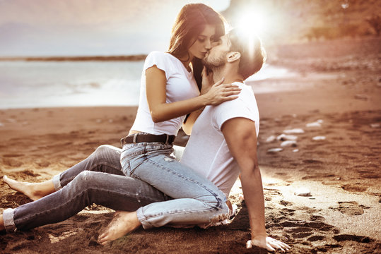 Fashion shot of an attractive couple kissing on a beach