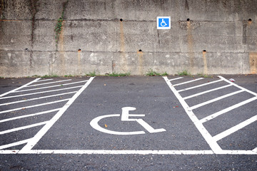empty parking lot with disabled parking sign on road.  parking for handicapped citizens.