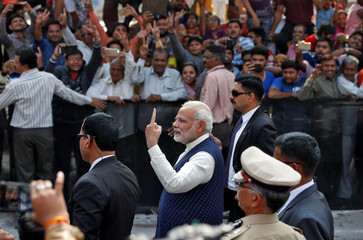 India's PM Modi shows his ink-marked finger after casting his vote outside a polling station during the last phase of Gujarat state assembly election in Ahmedabad