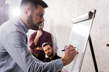 businessman writing something on flipchart in office