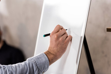 cropped image of businessman writing something on flipchart