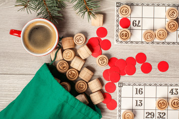 Wooden lotto barrels with bag, game cards, red chips and cup of coffee, Christmas fir tree branches