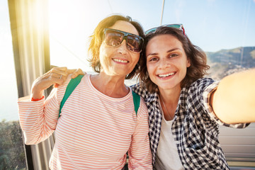 An elderly beautiful woman and her adult daughter travel together, do selfie on a mobile phone in the cockpit of a funicular during a summer holiday at sea