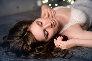 Brunette girl with evening makeup on the eyes closed and in a white nightgown lying on a dark bed upside-down.