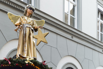 A statue of a cute little angel in a gold and silver robe, holding a star and wearing cool sunglasses on top of a christmas market booth.