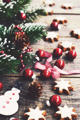 Festive decoration with snowman, pine cones, christmas red balls and gingerbread cookie stars
