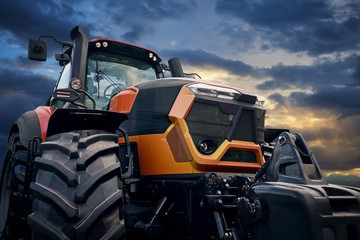 Fototapete - Powerful tractor on sunset background