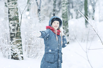 child  playing in the snow / the girl in warm sports clothes is playing with snow on a winter walk. Warm woolen hat, down jacket. Concept of a happy baby walk.