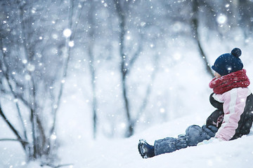 cheerful happy little girl on winter walk / little girl smiles and laughs in  snow, plays winter for a walk. The concept of  happy childhood. Warm sportswear down jacket, mittens, children's shoes