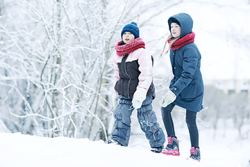 two sisters girls  winter for a walk / young girlfriends playing in the snow in the frost. The concept of childhood, friendship, family. Sports warm clothes, health immunity. Christmas morning.
