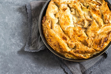 Simple homemade pie made of puff pastry with cheese and herbs