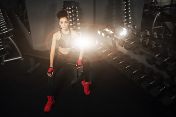 Iron girl. Fitness woman pumping up muscles with dumbbells. Fitness woman in the gym. Perfect physique athletic young girl with six pack, perfect abs, sexy shoulders and biceps. Crossfit woman