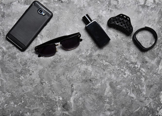 Accessories for a business woman on a concrete table. Purse, perfume, sunglasses, smart watch, smartphone, pen. Working space. Monochrome photography. Trend of minimalism. Top view.