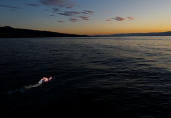 Naunton swims at sunset during a 70 km relay across Lake Leman in Evian-les-Bains