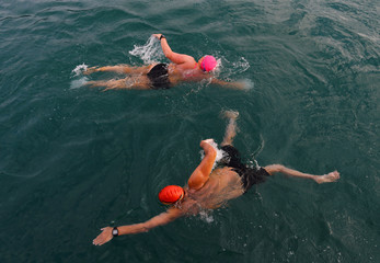 Swimmer Naunton starts her relay as team mate Gewert swims back to the boat during their relay across Lake Leman near Evian-les-Bains