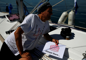 Swimmer Gewert holds a sign to communicate with team mate  Naunton during their 70 km relay across Lake Leman near St-Gingolph