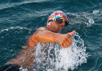 Swimmer Gewert gives a thumb up after receiving information from team mates during his shift of the 70 km relay swim across Lake Leman near Yvoire