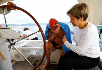 Swimmer Gewert reacts next to his wife Connie after struggling during a relay during their 70 km relay across Lake Leman near Evian-les-Bains