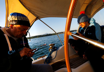 Swimmers Whitehead (R) and Gewert use their mobile phone while team mate Nicola Naunton swims a 70 km relay across Lake Leman from Montreux to Geneva near Yvoire